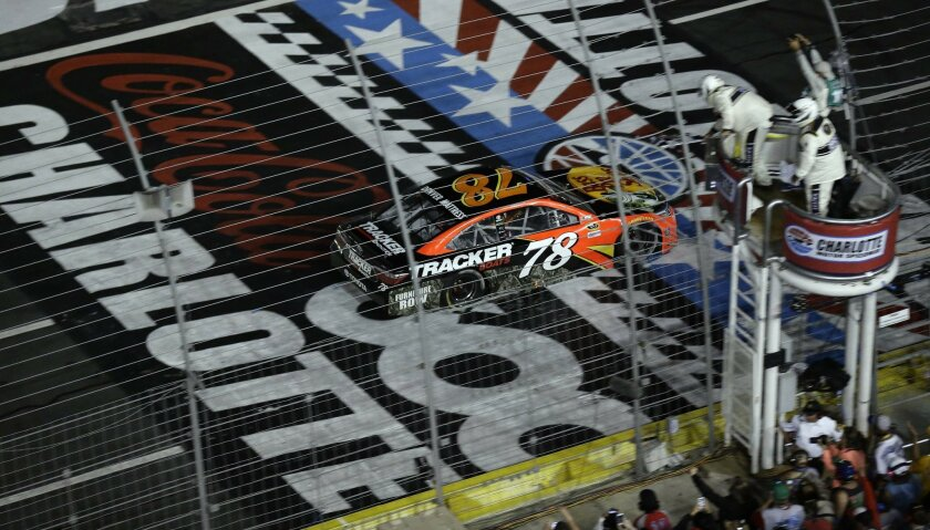 Martin Truex Jr. (78) crosses the finish line to win NASCAR Sprint Cup Series auto race at the Charlotte Motor Speedway in Concord, N.C., Sunday, May 29, 2016. (AP Photo/Gerry Broome)