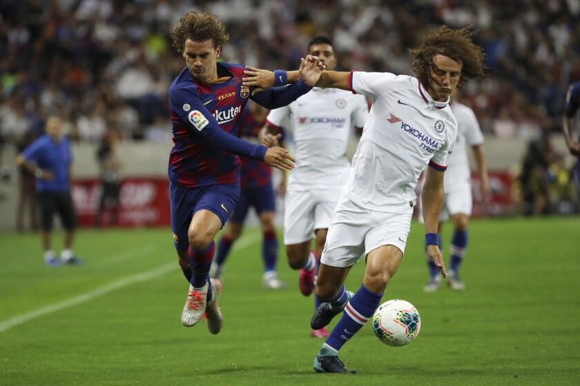 El defensor de Chelsea David Luiz, derecha, y el atacante de Barcelona Antoine Griezmann se disputan el balón en un partido de exhibición en Saitama, al norte de Tokio, el 23 de julio del 2019.