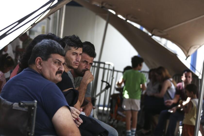 Refugiados esperan su turno para que un comité les de una audiencia de asilo en el servicio de Asilo de Grecia, en Atenas, el viernes 19 de agosto del 2016. La guardia costera griega rescató el viernes a docenas de migrantes después de que el barco que viajaban encalló en un islote desierto en la costa suroeste del país. (Foto AP /Yorgos Karahalis)