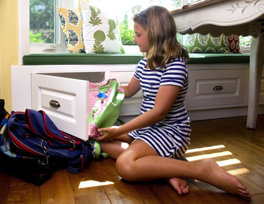 Jaden places her backpack in a storage area under the banquette.