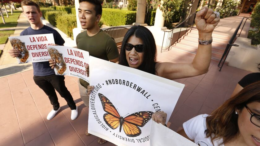 Protesters Will Goebel, from left, Rolando Delmundo, Yolanda Brown and Liz Martinez rally Tuesday outside the U.S. 9th Circuit Court of Appeals in Pasadena, where justices heard arguments in a case involving the Trump administration's effort to build a border wall.