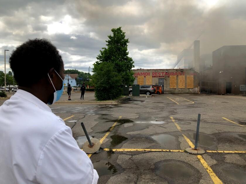 Abdishakur Elmi watches firefighters try to extinguish a blaze next to his Somali restaurant Friday.