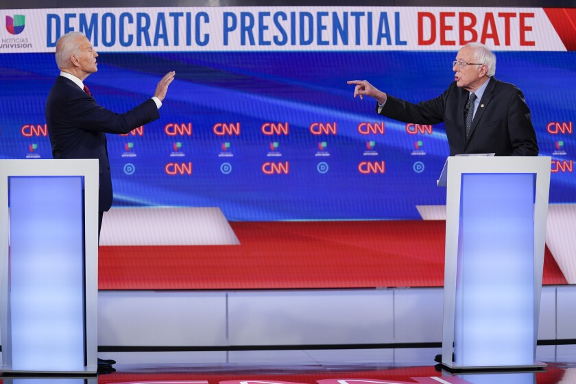 Former Vice President Joe Biden, left, and Sen. Bernie Sanders, I-Vt., right, participate in a Democratic presidential primary debate at CNN Studios in Washington, Sunday