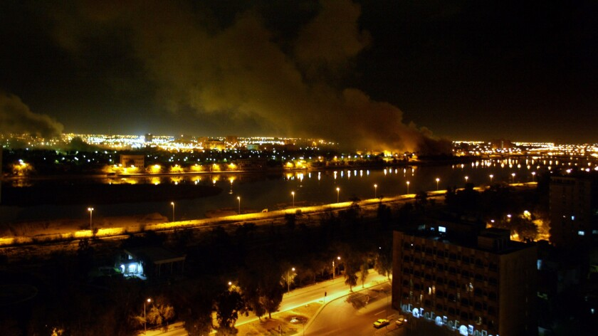 On March 20, 2003—the second night of war against Iraq—bombs fall on government buildings located along the Tigris River in Baghdad, leaving a plume of smoke rising in the air. Multiple bombs left several buildings in flames and others completely destroyed.