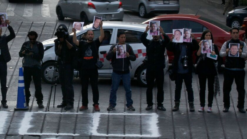 Journalists hold up photos of Javier Valdez and other slain colleagues at the Angel of Independence