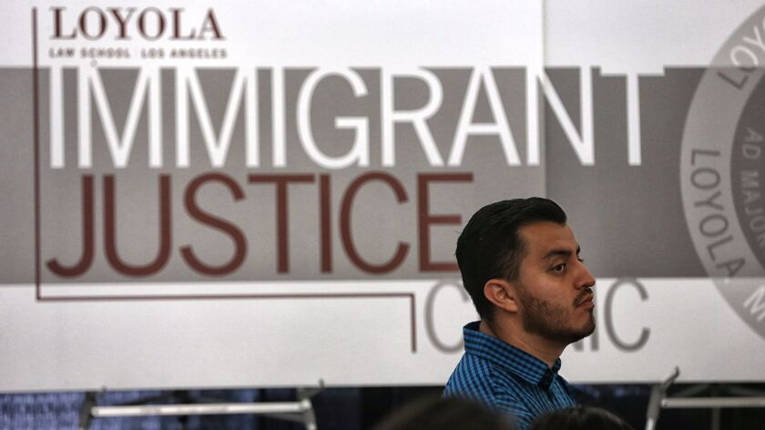 Christian Perez, 30, consults with volunteers at the Loyola Immigrant Justice Clinic at Loyola Law S