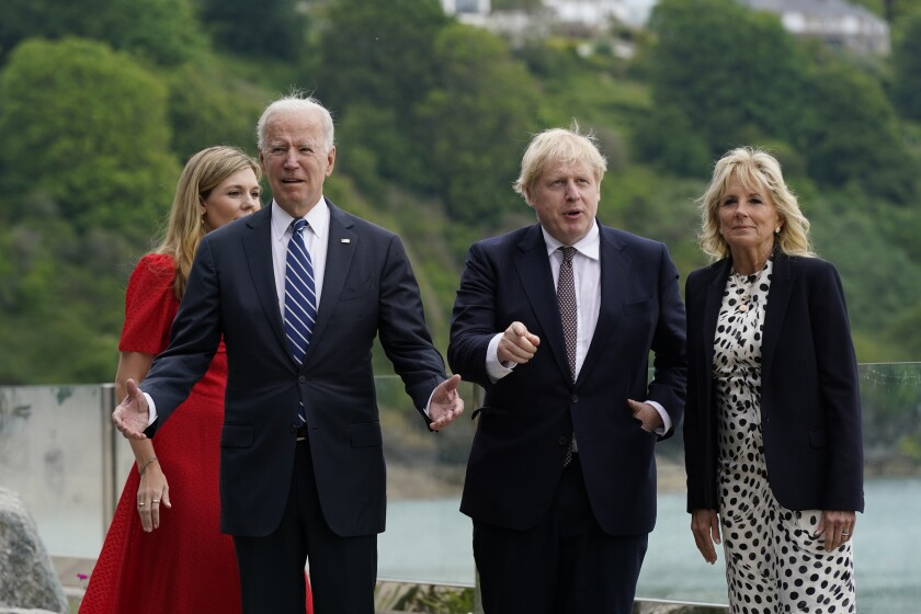President Biden and Boris Johnson walk together, accompanied by their spouses.