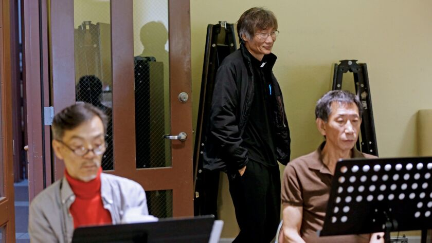 Seon Jin Kim, left, and the Rev. John Kim, center, are shown at choir practice at St. James Episcopa