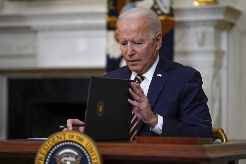 President Biden closes a folder after signing an executive order