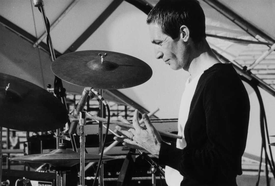A black-and-white photo of drummer Charlie Watts at his kit in 1975.