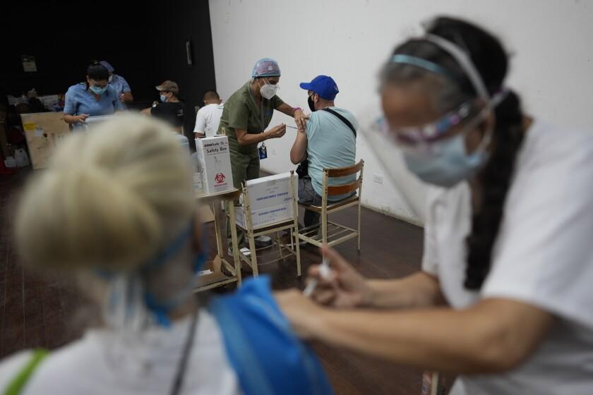 Trabajadores de la salud administran a las personas una dosis de la vacuna Sinopharm para el COVID-19 en Caracas, Venezuela, el viernes 3 de septiembre de 2021. (AP Foto/Ariana Cubillos)