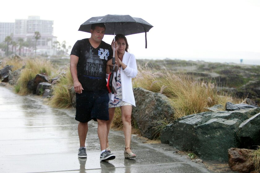 Gabe Gonzalez and Joanna Gonzalez of Arizona take cover from the rain along Coronado on Aug. 24, 2016.