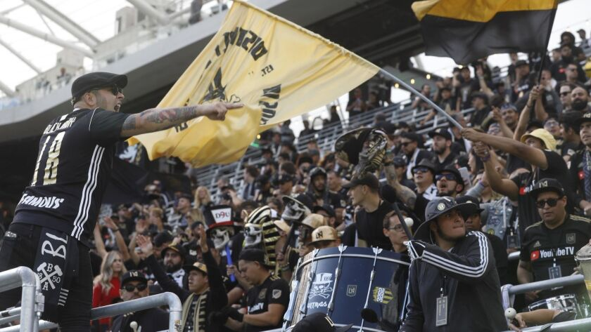 Jimmy Lopez, left, joins fans in a cheer before LAFC's game against the Seattle Sounders in the first game at the brand-new Banc of California Stadium.