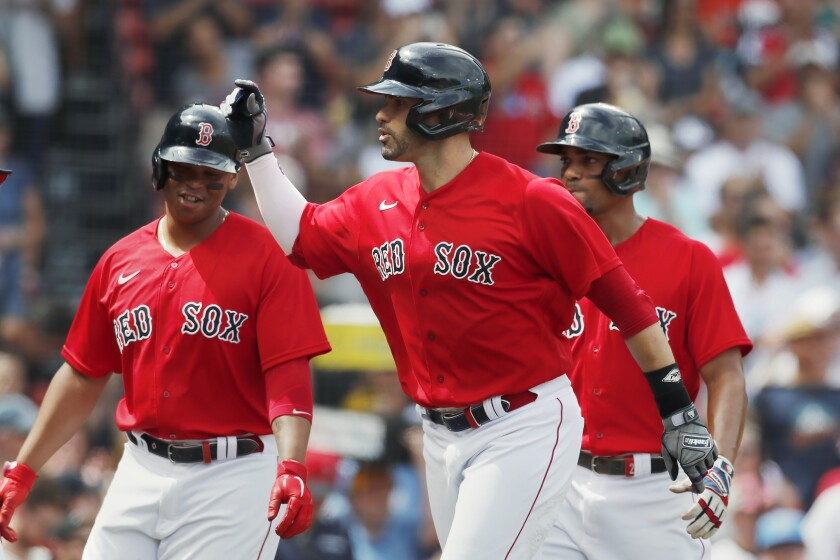 Boston Red Sox's J.D. Martinez, center, celebrates his three-run home run that also drove in Rafael Devers, left, and Xander Bogaerts, right, during the first inning of a baseball game against the Baltimore Orioles, Sunday, Aug. 15, 2021, in Boston. (AP Photo/Michael Dwyer)