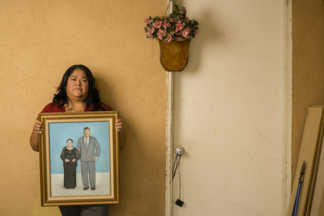 Rosario Rodríguez hold a picture of her parents, Herminia and Martin Rodriguez in her garage in Three Rocks.