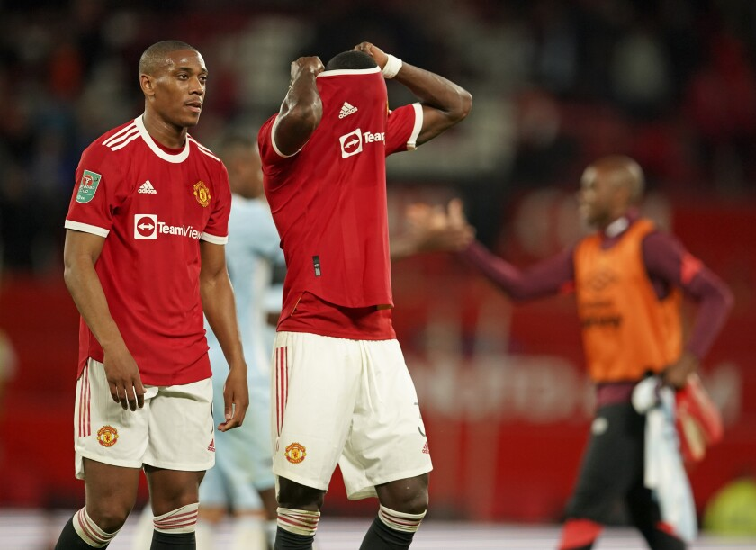 Manchester United's Anthony Martial, left, and Eric Bailly leave the pitch at the end of the English League Cup soccer match between Manchester United and West Ham at Old Trafford in Manchester, England, Wednesday, Sept. 22, 2021. West Ham won the match 1-0. (AP Photo/Dave Thompson)