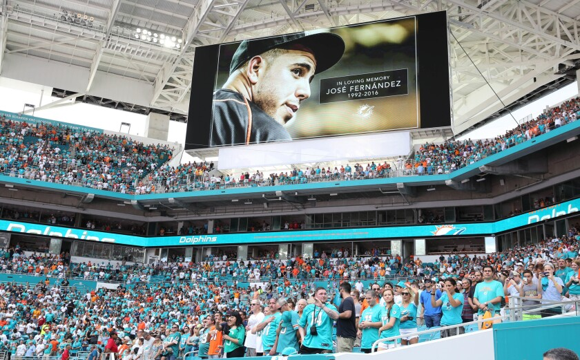 Miami Dolphins fans stand for a minute of silence for Miami Marlins pitcher Jose Fernandez, who was killed early Sunday, Sept. 25, 2016 in a boating accident in Miami. (AP Photo/Marta Lavandier)