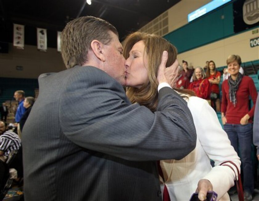 Liberty University head men's basketball coach Dale Layer kisses his wife Brenda after his team defeated Charleston Southern 87-76 to win the NCAA basketball Big South Championship on Sunday March 10, 2013 in Conway, S.C. (AP Photo/Willis Glassgow)
