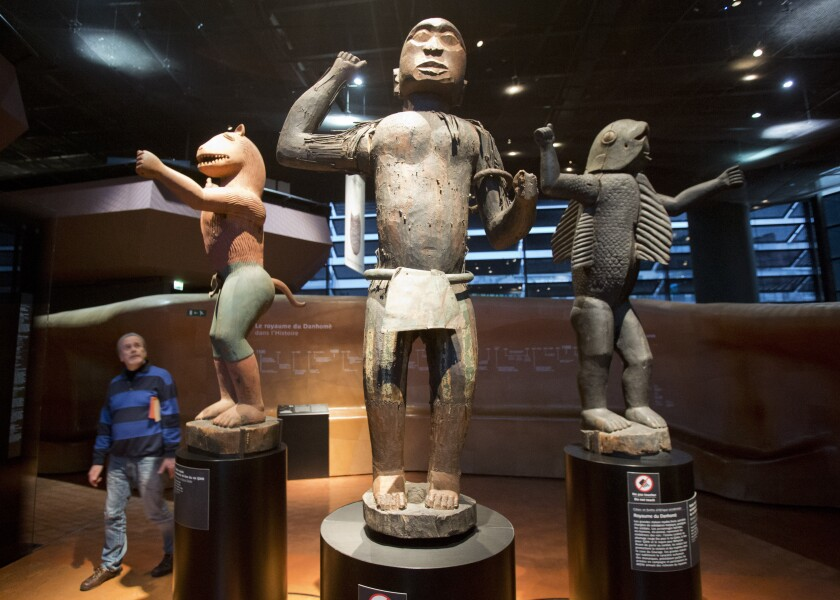 In this Friday, Nov. 23, 2018 file photo a visitor looks at wooden royal statues of the Dahomey kingdom, dated 19th century, at Quai Branly museum in Paris, France. France will return 26 African artworks to Benin later this month as part of long-promised efforts to give back artwork taken from Africa during the colonial era. (AP Photo/Michel Euler, File)