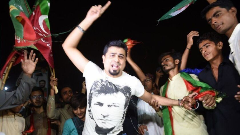 Supporters of Pakistan's cricketer-turned politician Imran Khan celebrate in Karachi on July 26, 2018, as Khan claimed victory in a general election.