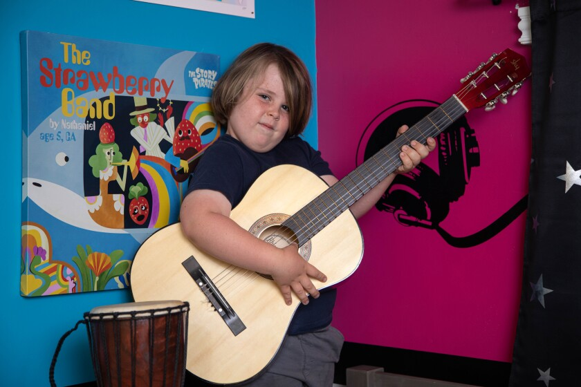 Nathaniel Jacobs is shows playing the guitar at his home in El Cajon.