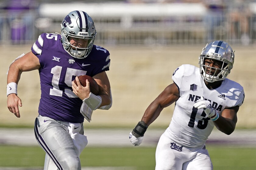 Kansas State quarterback Will Howard (15) gets past Nevada defensive back Jordan Lee (13) to run for a first down during the second half of an NCAA college football game Saturday, Sept. 18, 2021, in Manhattan, Kan. (AP Photo/Charlie Riedel)