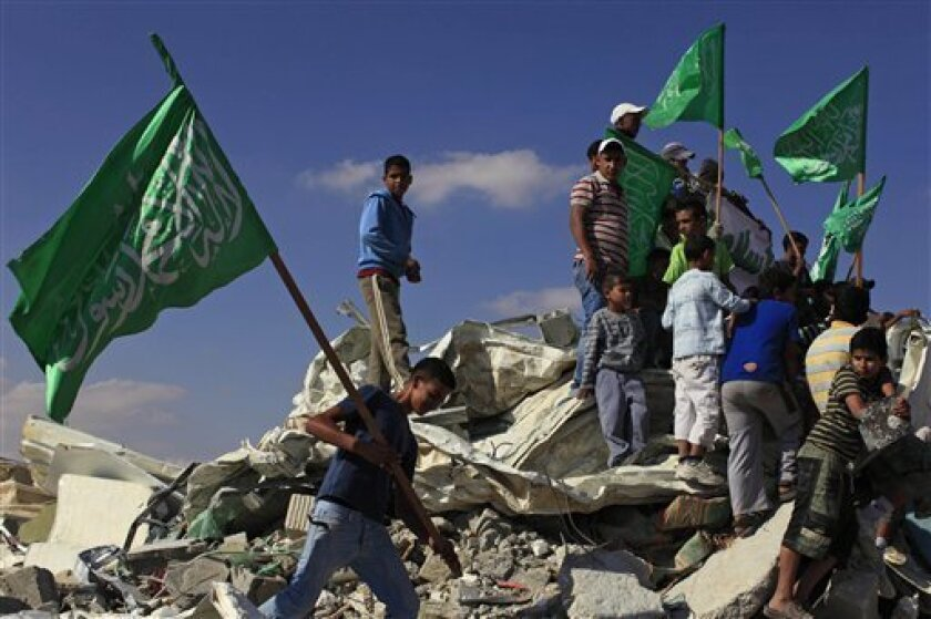 Israeli Arab youths, holding green Islamic flags, stand on the rubble of a mosque, demolished by the Israeli police, in the Bedouin city of Rahat, southern Israel, Sunday, Nov. 7, 2010. Israeli police say they demolished an illegally built mosque in the southern Bedouin city of Rahat, touching off rock-throwing protests by residents. (AP Photo/Tsafrir Abayov)