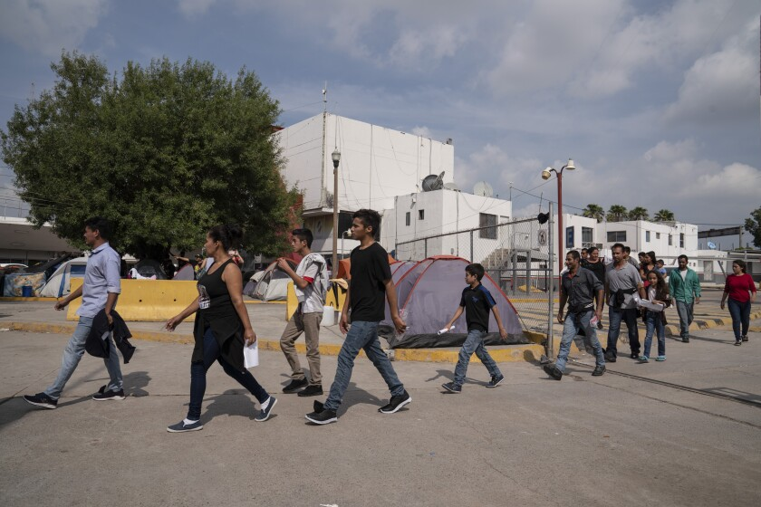 Asylum seekers who have just been sent back from the U.S. to Mexico walk to Human Repatriation facilities on Aug. 24, 2019, in Matamoros.
