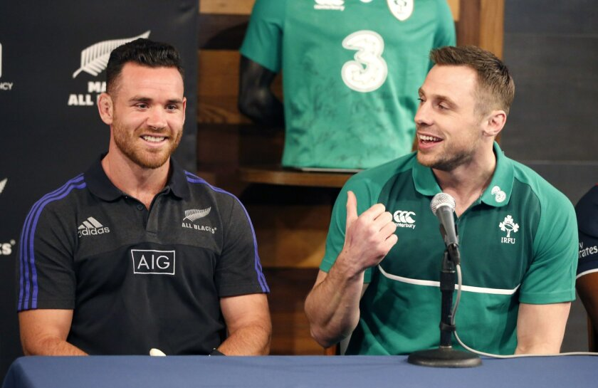 New Zealand All Blacks' Ryan Crotty, left, listens to Ireland's Tommy Bowe during a news conference at Chicago;'s Soldier Field Tuesday, Feb. 16, 2016, announcing that the All Blacks will play Ireland at the historic stadium in November. (AP Photo/Charles Rex Arbogast)