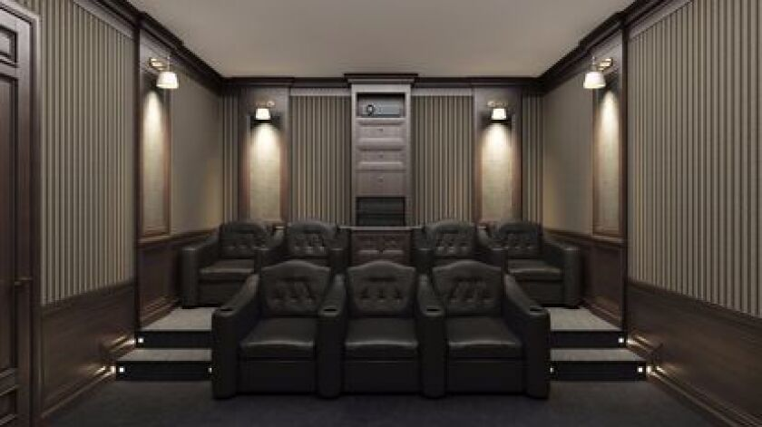 Interior of luxury home theater with lounge chairs.