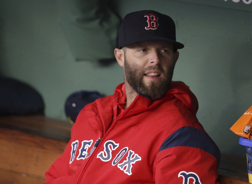 FILE - In this Tuesday, April 30, 2019, file photo, Boston Red Sox's Dustin Pedroia sits in the dugout prior to a baseball game at Fenway Park, in Boston. Pedroia is hoping to return to the Boston Red Sox in 2020 after playing in just nine games during the past two seasons because of his injured left knee. (AP Photo/Charles Krupa, File)