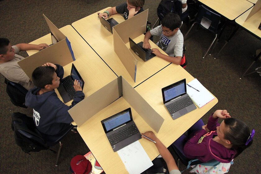 Students in a sixth grade classroom at Veterans Elementary school practice testing to prepare for the new exams that will measure Common Core academic standards.  The partitions are used to give test takers privacy and prevent cheating.