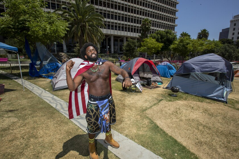 Jason Morales, 34, of Pacoima stands amid the Grand Park camp whose theme is Black unity.