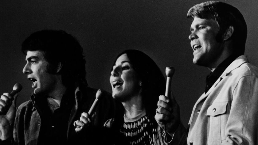 "Neil Diamond, left, Cher, and Glen Campbell performing on ""The Glen Campbell Goodtime Hour."""