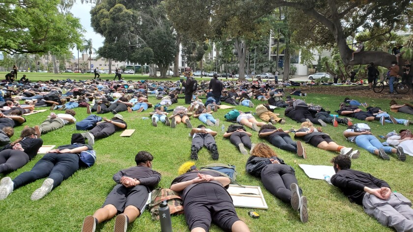 Youth protesters simulated the pose of a person being arrested Monday afternoon near Balboa Park after marching to the area from San Diego City College in downtown San Diego.