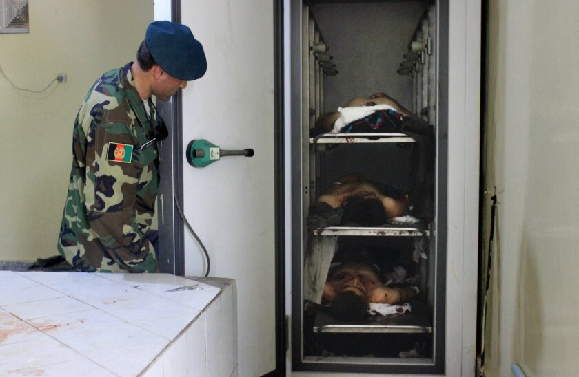 An Afghan soldier looks at lifeless bodies of men who were killed by Taliban militants in Kunduz province northern of Kabul, Afghanistan, Tuesday, May 31, 2016. An Afghan official says the Taliban have attacked several buses on a road in the country's north, killing many people and abducting at lea