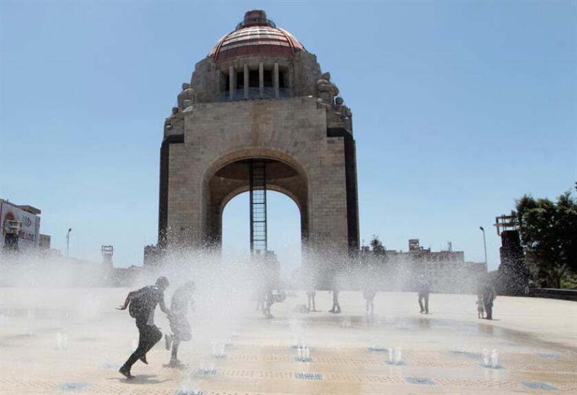 Un grupo de personas se refresca en la fuente de la explanada del Monumento a la Revolución en Ciudad de México (México). EFE/Archivo