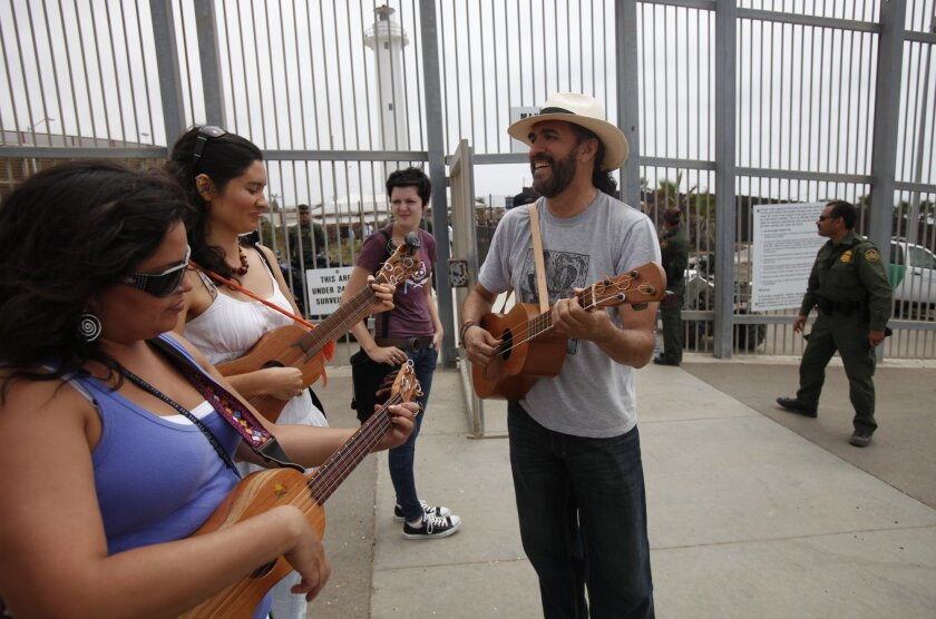 Jorge Castillo plays with other members of his music group Saturday outside the entrance to Friendship Park before entering the gates to play with musicians on the Tijuana side. James Gregg • u-t