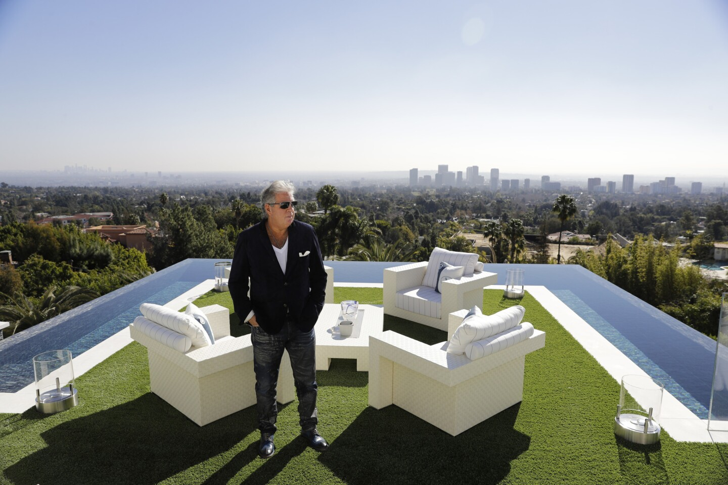 In this Thursday, Jan. 26, 2017, photo, developer Bruce Makowsky poses for a photo on the balcony off the master bedroom of a $250 million mansion he built in the Bel-Air area of Los Angeles. The mansion, the most expensive home listed in the U.S., includes 12 bedroom suites, 21 bathrooms, five bars, three gourmet kitchens, a spa and an 85-foot infinity swimming pool with stunning views of Los Angeles.
