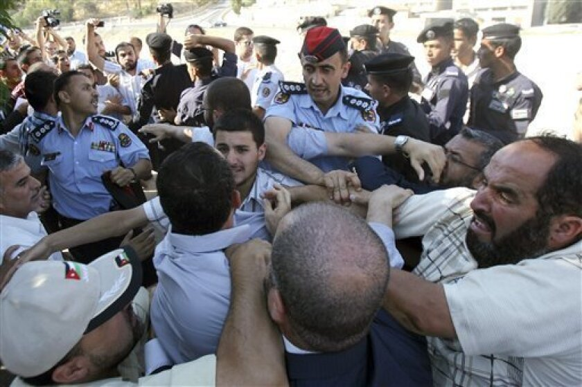 Jordanian police clash with protesters to prevent them from throwing eggs on the Parliament building during a demonstration demanding the dismissal of lawmakers and the Prime Minister in Amman, Jordan, Thursday, June 30, 2011. Jordanians are angry that deputies cleared Prime Minister Marouf al-Bakhit of involvement in a casino scandal during his previous 2005-2007 stint as premier. At the time, his Cabinet approved the country's first casino in violation of Islamic law.(AP Photo/ Nader daoud)