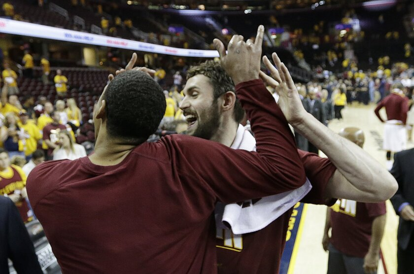 Cleveland Cavaliers' Kevin Love, center, and Channing Frye celebrate after Cleveland defeated the Toronto Raptors 116-78 in Game 5 of the NBA basketball Eastern Conference finals Wednesday, May 25, 2016, in Cleveland. (AP Photo/Tony Dejak)