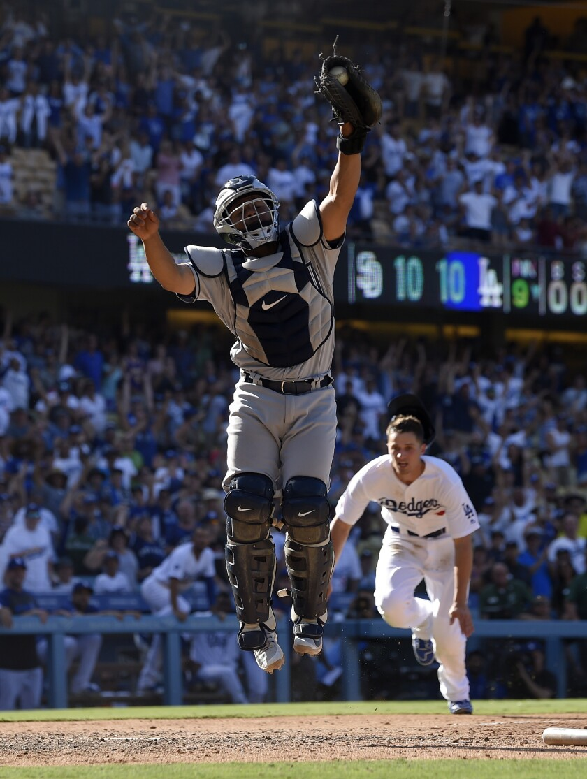 Padres catcher Francisco Mejia, who finished 3-for-4, corrals a throw as the Dodgers' Corey Seager prepares to score the winning run in a wild 11-10 game Sunday at Dodger Stadium.