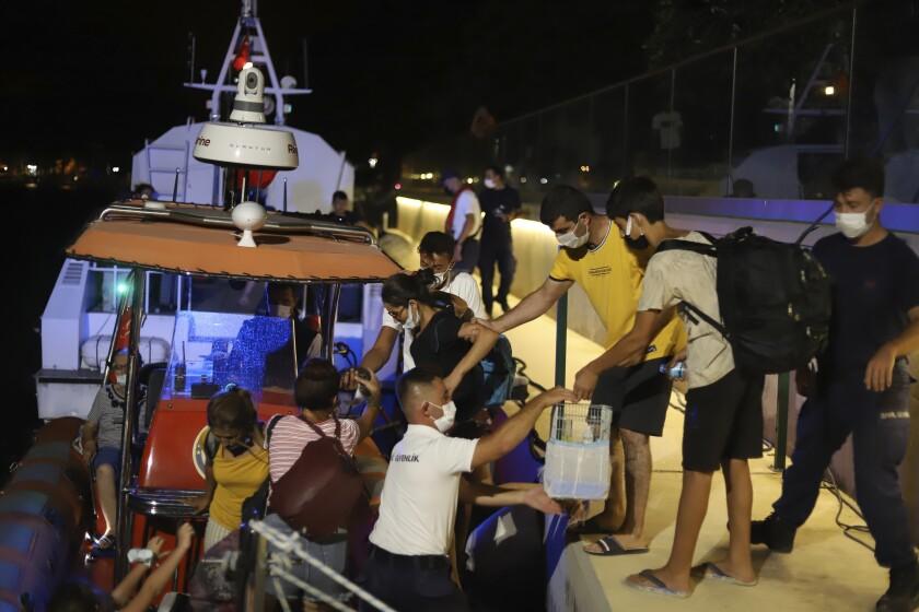 Gente evacuada en barco después de que los incendios llegaran a la central eléctrica de Kemerkoy, en Milas, suroeste de Turquía, la noche el miércoles 4 de agosto de 2021. (AP Foto/Cem Tekkesoglu)
