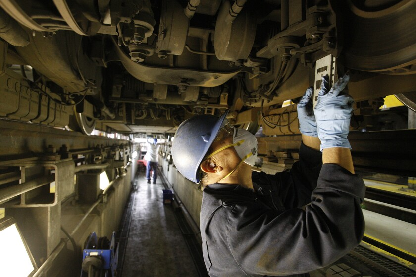 Maintenance specialist Thi Vu installs new friction brake shoes on a Metro Blue Line light-rail car.