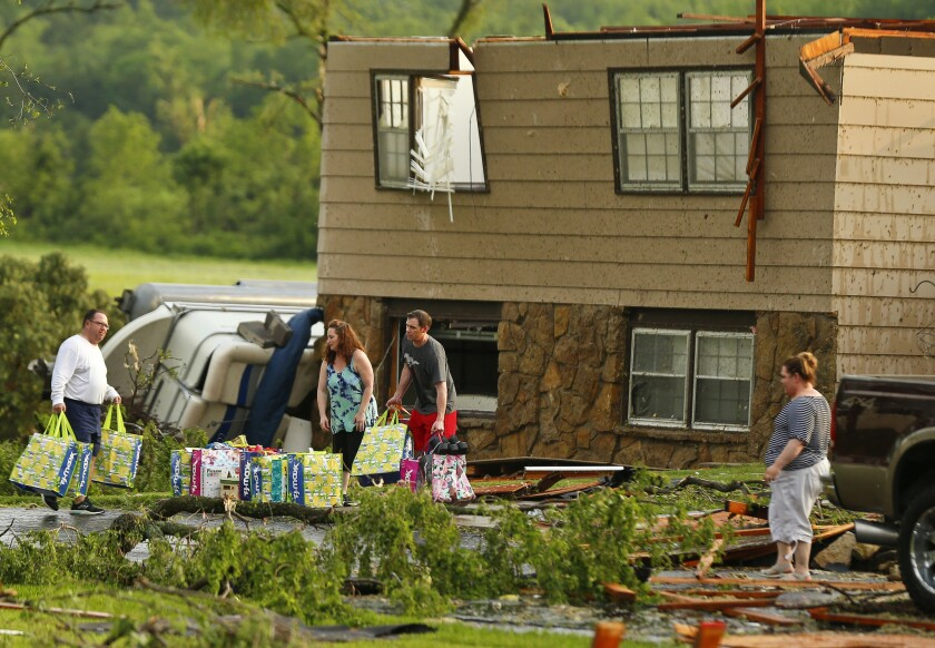 A family tries to gather their belongings after a tornado destroyed their home on Tuesday, May 28, 2