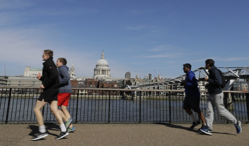 People running along the River Thames in London