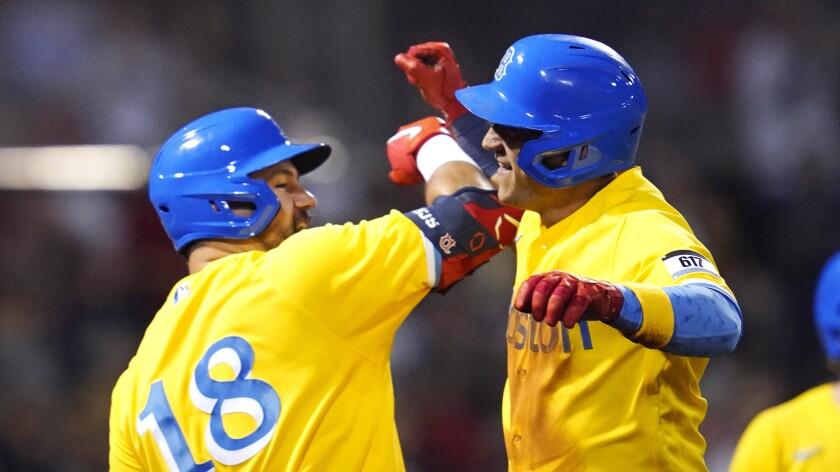 El cubano José Iglesias (derecha) es felicitado por Kyle Schwarber, su compañero en los Medias Rojas de Boston, tras anotar ante los Mets de Nueva York el miércoles 22 de septiembre de 2021 (AP Foto/Charles Krupa)