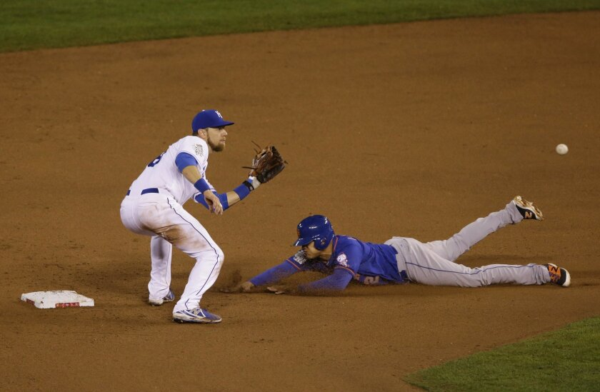 New York Mets' Juan Lagares (12) steals second base on a late throw to Kansas City Royals second baseman Ben Zobrist during the eighth inning of Game 1 of the Major League Baseball World Series Tuesday, Oct. 27, 2015, in Kansas City, Mo. (AP Photo/Orlin Wagner)