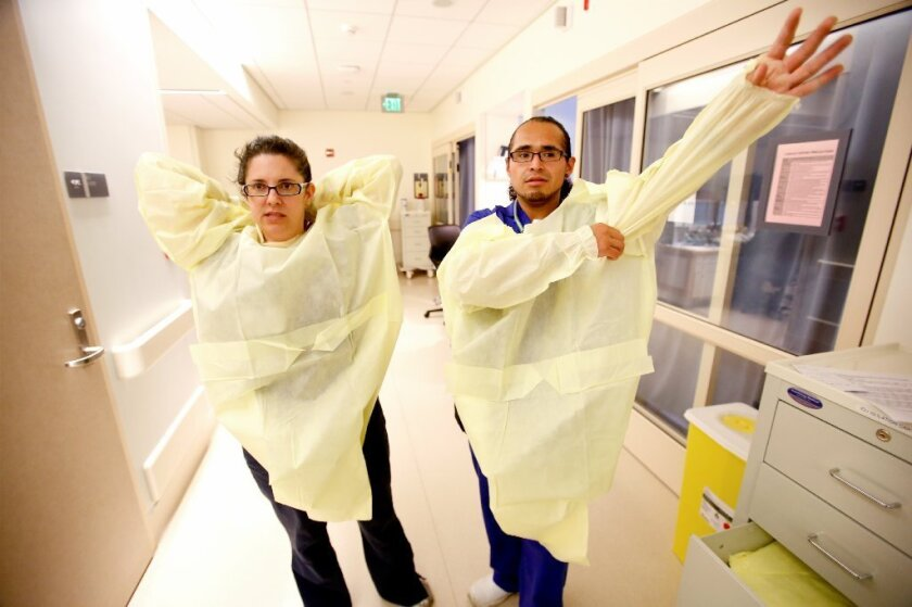 Nurses gown up before seeing a patient. A new study finds that hospital workers are at risk of becoming contaminated with dangerous pathogens, even when they put onand remove their gowns and gloves correctly.