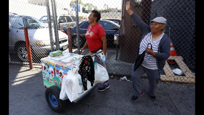 Bertha Arce, left, and her friend Rosa Calderon wave at the police officer who repeatedly gives Calderon tickets.